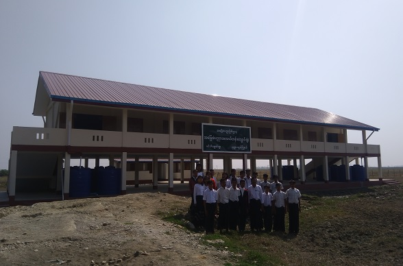 A school class poses for a photo in front of a rebuilt school.