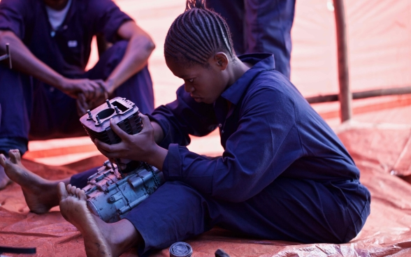 A young woman sits on the ground repairing a motor.