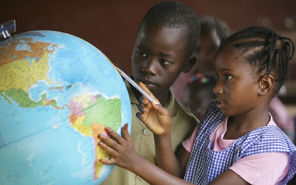 Children looking at a globe in a classroom.