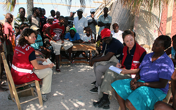 Two Swiss experts listen to a Haitian woman in the presence of other local people.