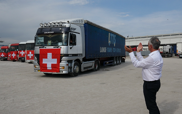 Federal Councillor Didier Burkhalter applauds as the Swiss humanitarian convoy sets off.