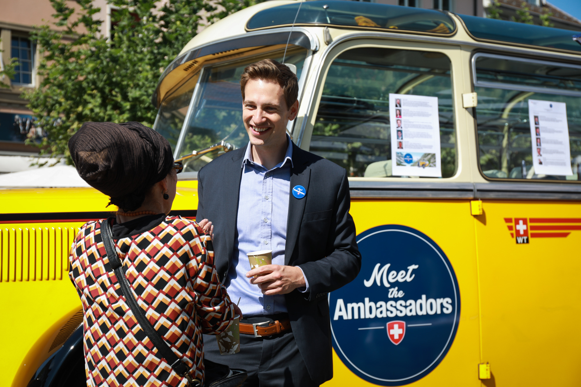 An ambassador talks to a visitor; in the background is the bus Meet the Ambassador